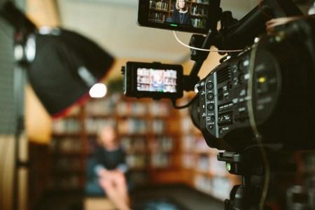 een vrouw die gefilmd wordt als illustratie bij een blog over de voorganger in online kerkdiensten