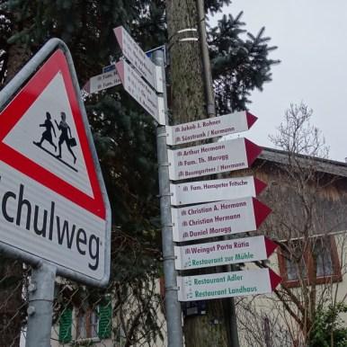 Ihr kennt das bestimmt? Die Schweizer und ihre Wegeweiser. Hier mal nicht im klassischen geld oder rot-weiss-rot. Sondern Weinrot=Weinbaudorf=Weinbauer. Ich hole Mini-Me von der Spielgruppe ab.