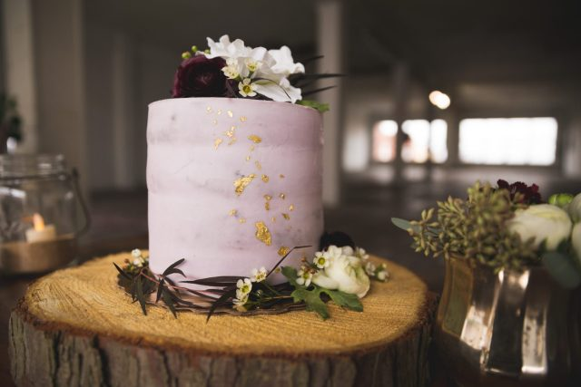Pink wedding cake with gold flecks, flowers on top, and set on top of wooden base.