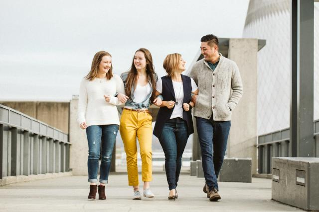 Family with two teenage girls walk with linked arms, laughing, along a cement walkway in Tacoma