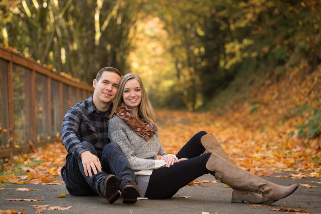 Young husband and wife sit next to each other on a walking path with lots of fall leaves and trees around them.