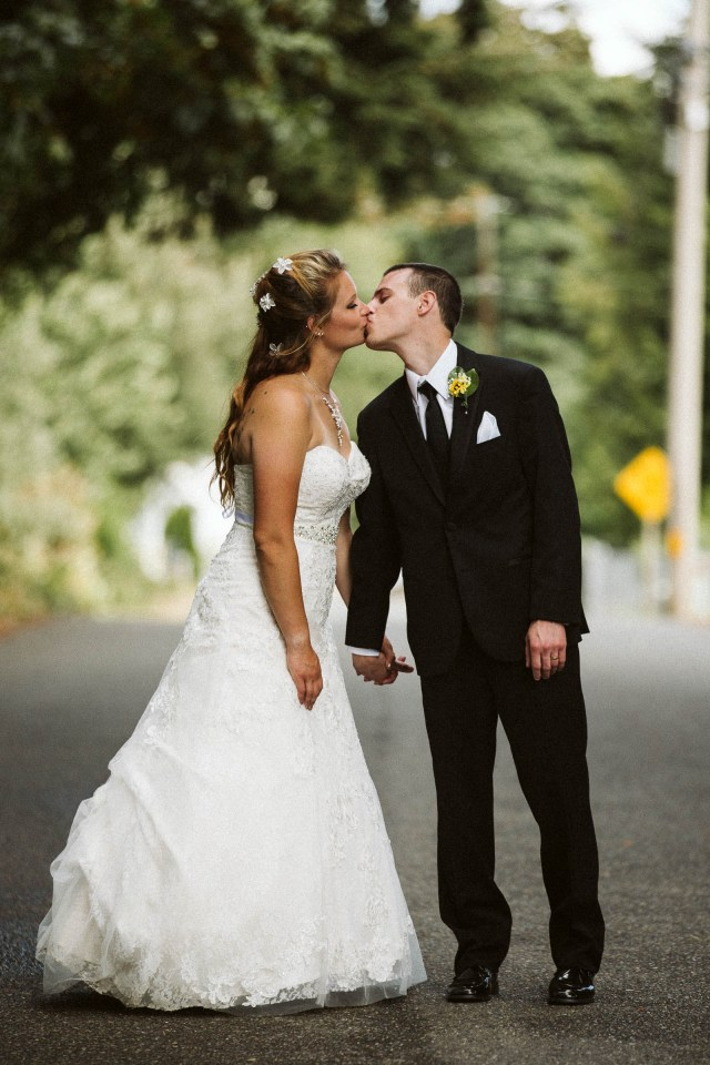 Washington Bride and groom stand together kissing in road