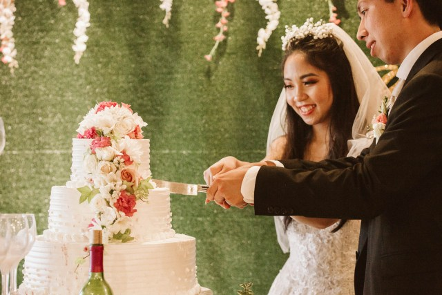 Vietnamese bride and groom cut the top tier of a wedding cake