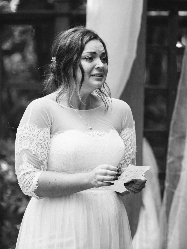 Bride cries during vows during wedding ceremony.