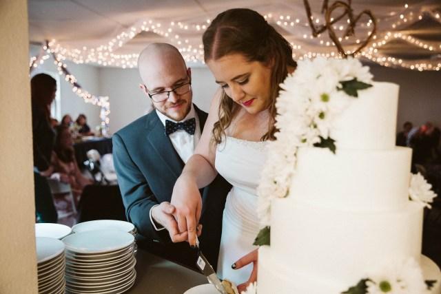 Portland bride and groom cut three tier, white wedding cake