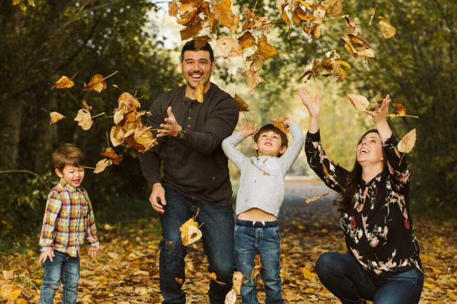 Family with two young boys throw leaves up into the air with smiles
