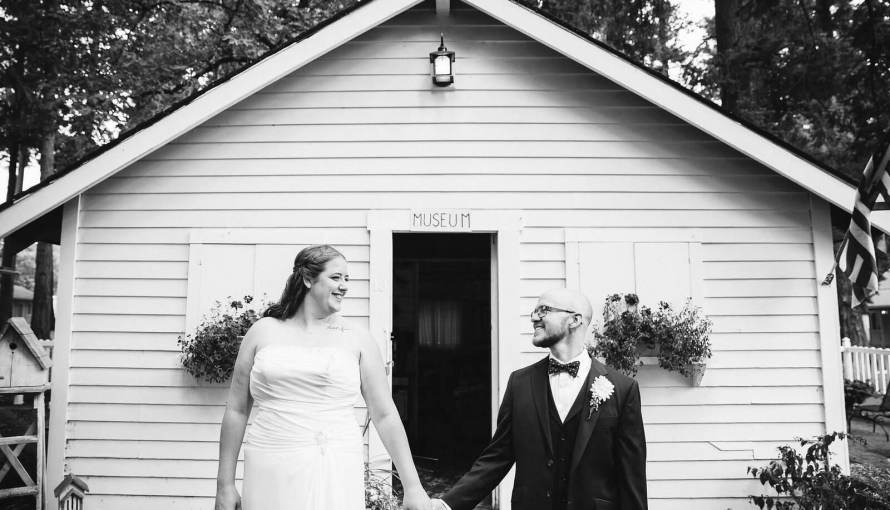 Bride and groom stand hand in hand in front of white cabin in a black and white picture.