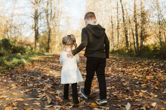 Boy and girl walk away on path with fall leaves all over