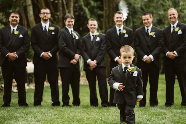 Ring bearer walks in front of the groomsmen and groom