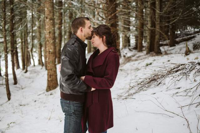 Man kisses woman's forehead while holding each other in snowy Washington forest