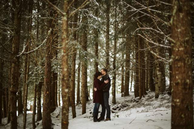 Husband and wife stand together intimately in under trees in snowy Washington forest.