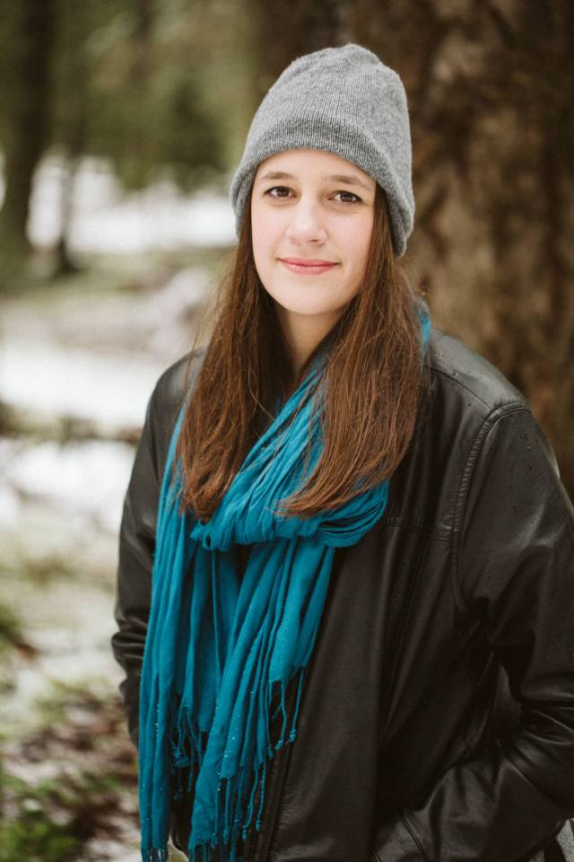 Portrait of teen girl with leather jacket, blue scarf, and grey beanie.