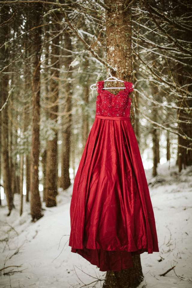 Red ballroom prom dress hangs on tree in forest with snow