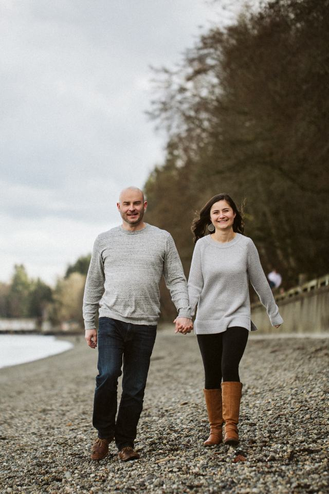 Man and fiance walk along rocky beach with forest on one side.