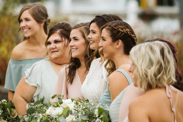 bride and bridesmaids stand in a line looking at a photographer to the side