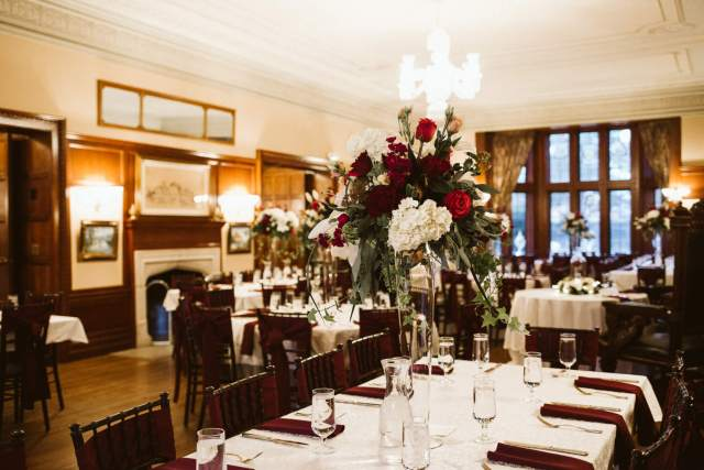 Wedding tables in a smaller castle dining room with large vases full of white and red roses