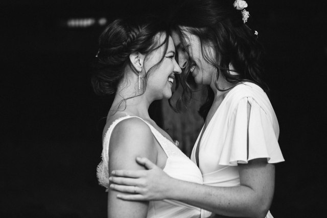 Black and white picture of two brides face each other with foreheads together and laugh.