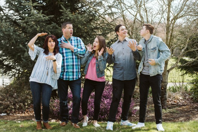 Family with mom, dad, a daughter, and two sons pose goofy in front of trees on grass.