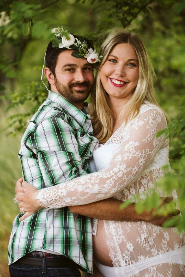 Husband and pregnant wife hug while husband wears white flower crown.