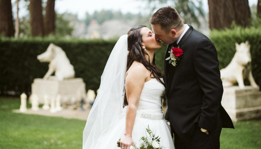 Groom and Bride stand together in manicured lawn garden and kiss during first look.