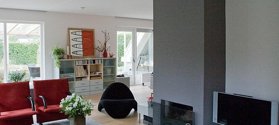 Grijs geschilderde haardwand in woonkamer na kleuradvies