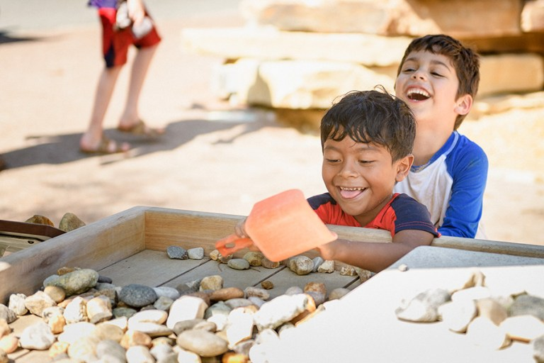 A boy digs through a pile of stones with an orange shovel, while another boy laughs behind him.