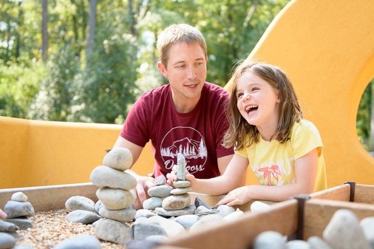 An adult and a girl are building together with rocks and laughing.