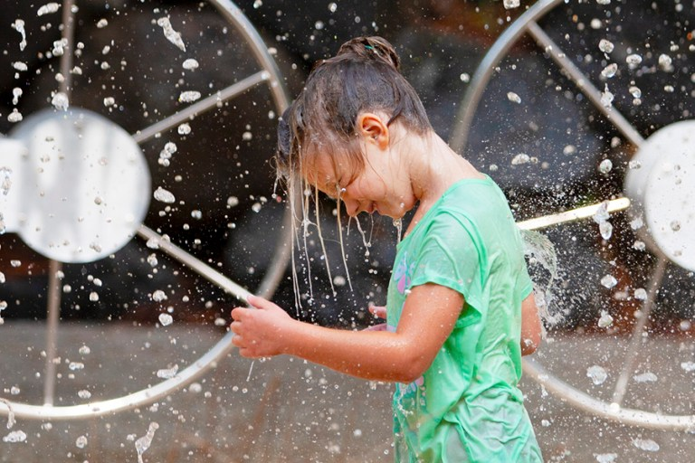 A girl stands under a waterfall and is completely soaked.