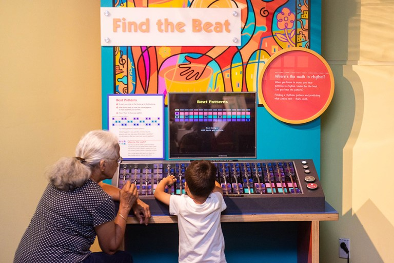 A grandmother and young boy play with a beat making machine.