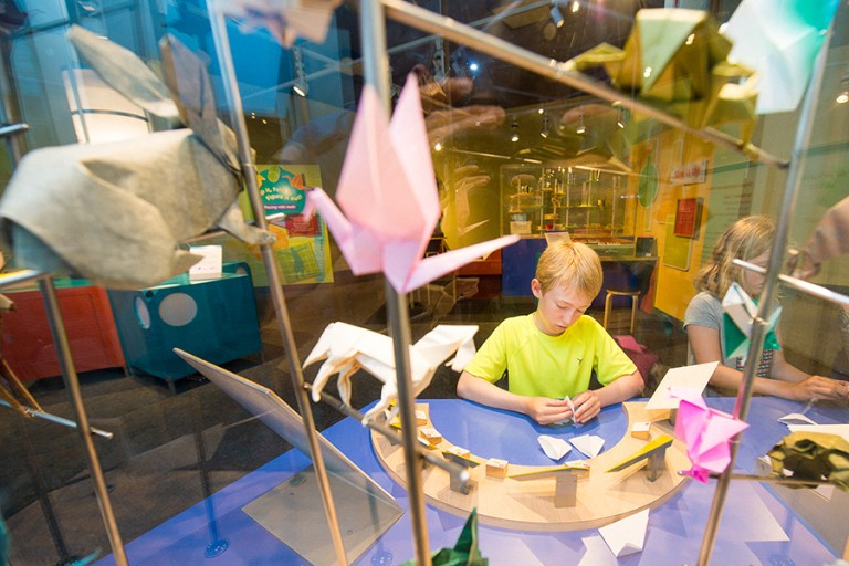 A boy folds an origami shape at a table surrounded by other origami creations.