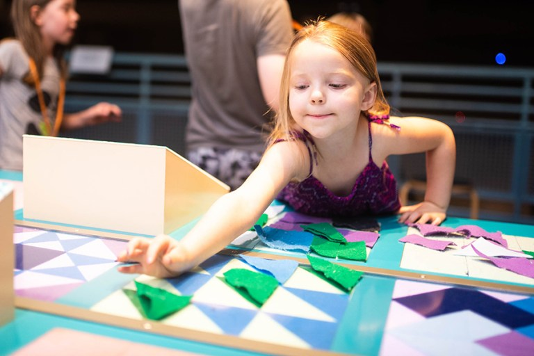 A young girl places a piece of felt on a patterned quilt square.