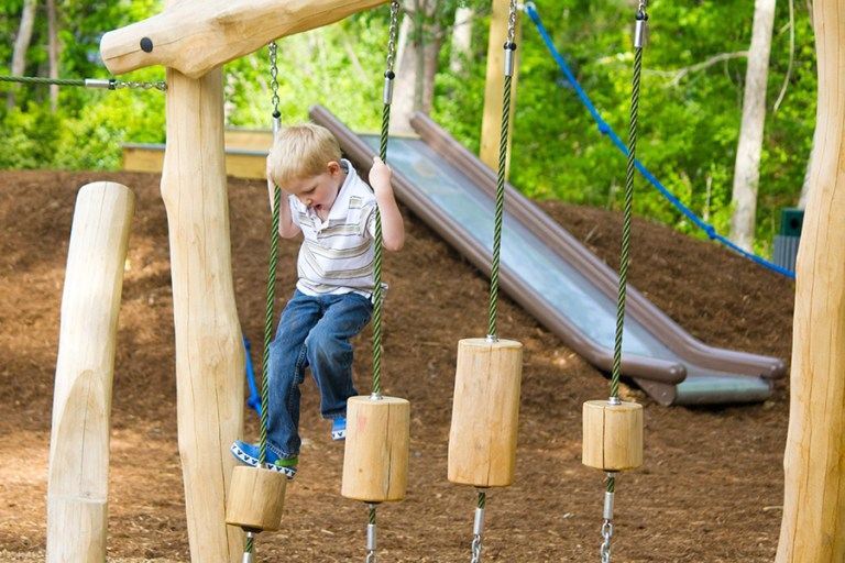 A young boy crosses a series of hanging logs.
