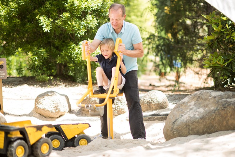 A man and boy operate a yellow digging machine in a sandbox near some toy dump trucks.