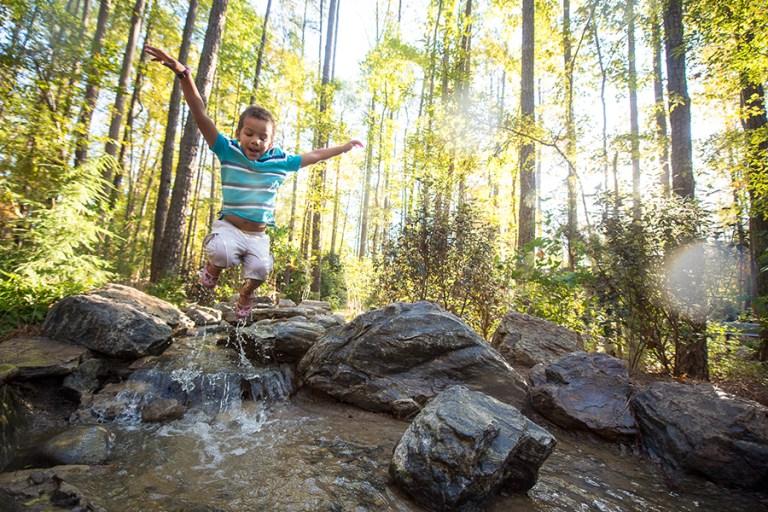 A boy jumps into a stream making a splash.