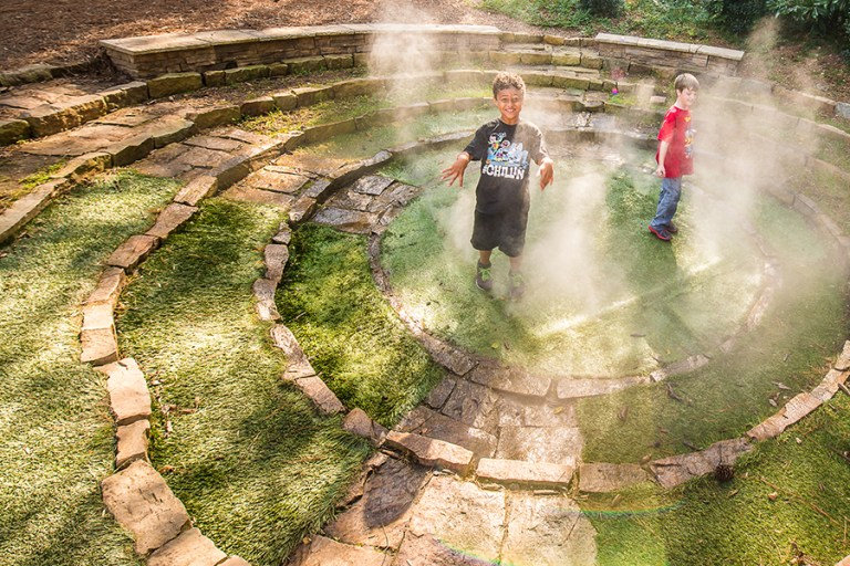 Two boys stand in the middle of concentric circles of rocks while mist swirls around them.