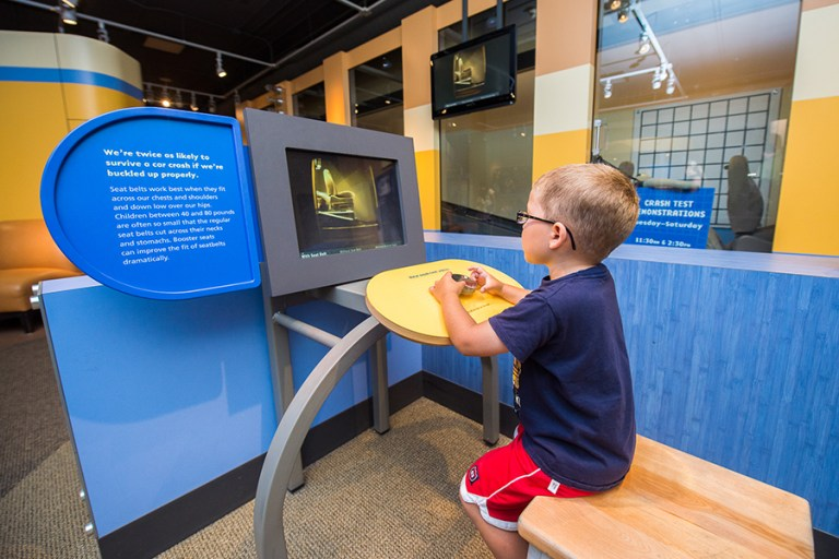 A young boy looks at a video of a crash test dummy.
