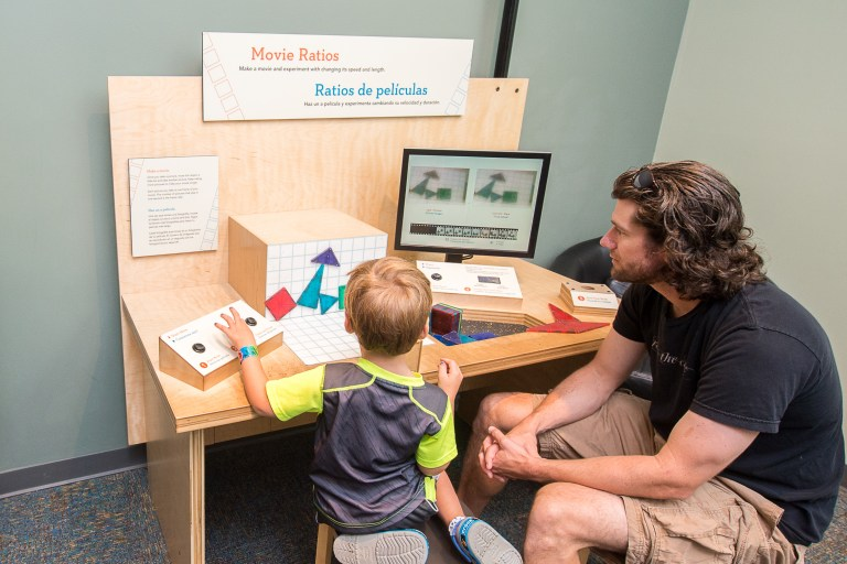 A man and boy look at a monitor at a table where they are making stop motion animation.