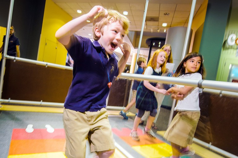 Excited boy races a girl on a rainbow colored floor.