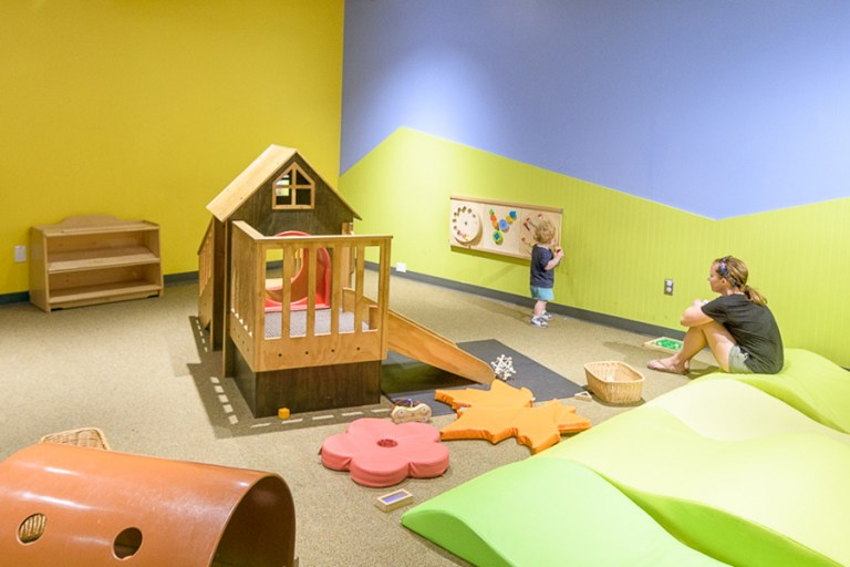 A mother watches a small child explore a room with colorful mats and a small house.