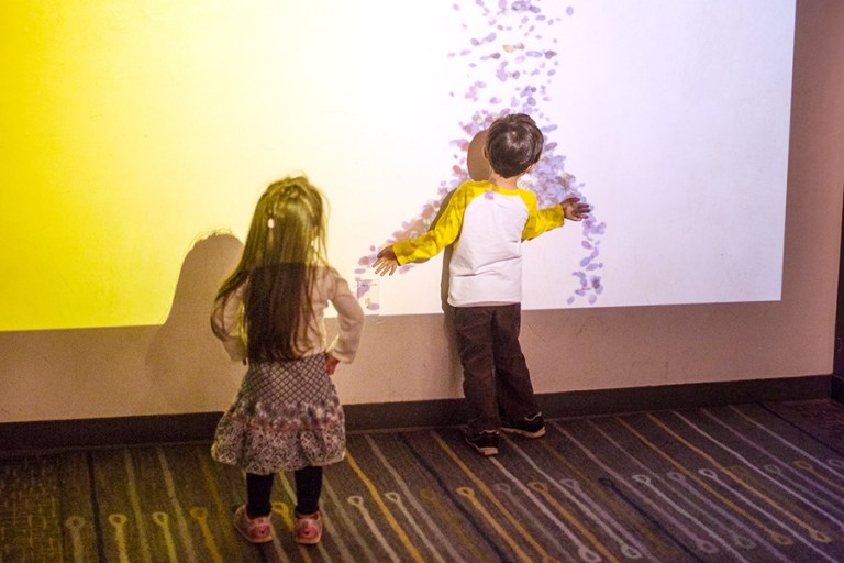 Two kids make shadows against a wall while colorful sand images fall around them.