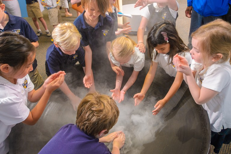 A group of school children gathers around a bowl and touches a cloud like fog.