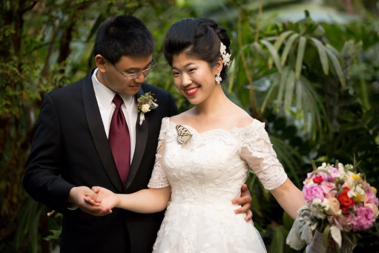 Bride and groom pose in butterfly house. A butterfly has landed on bride's dress.