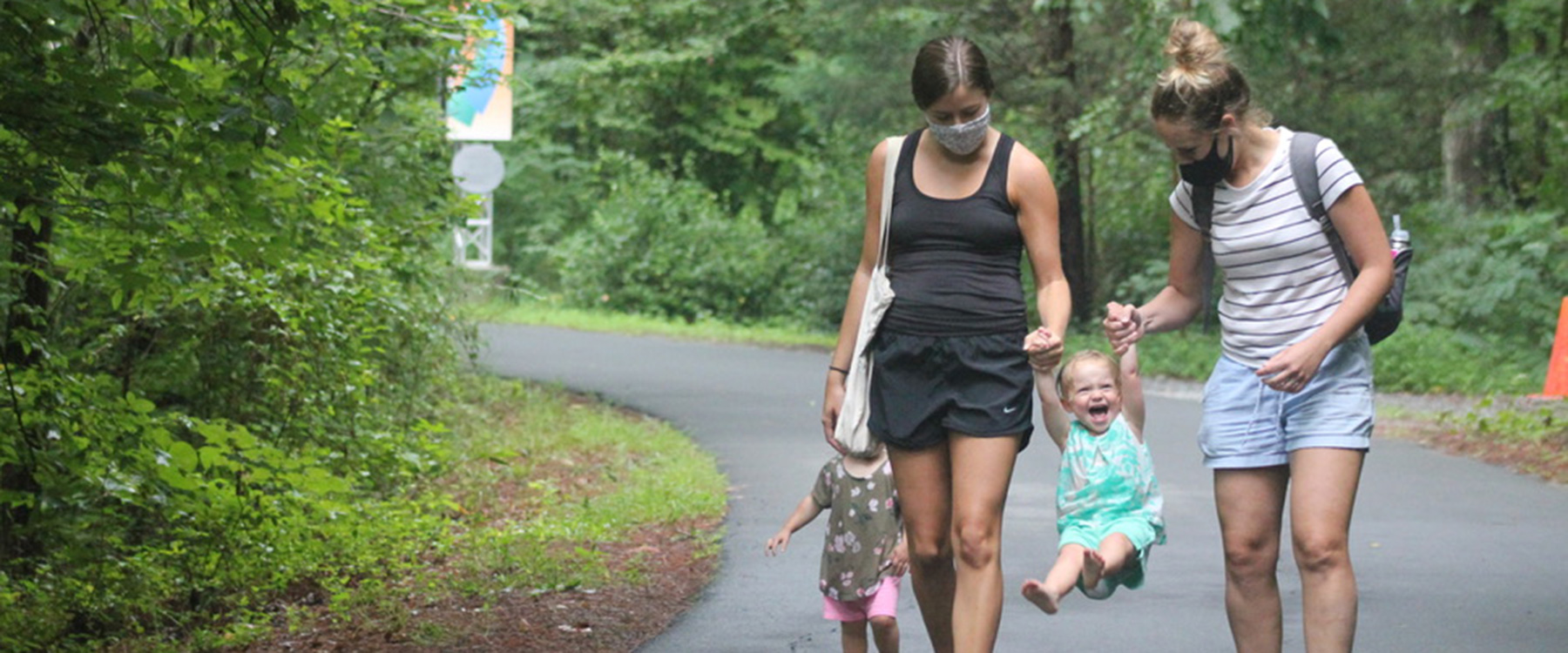 Two women and a kid walking along the path