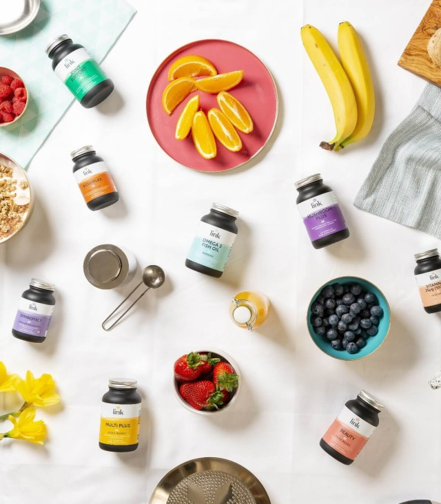 Fruits and supplements laid out on a tablecloth