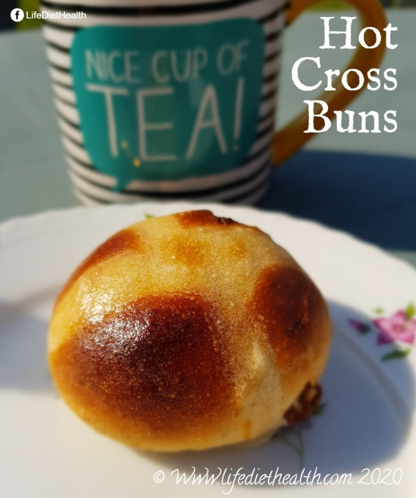 Cooked hot cross bun on a white flower patterned plate. Mug of tea behind the bun - mug says 'nice cup of tea'