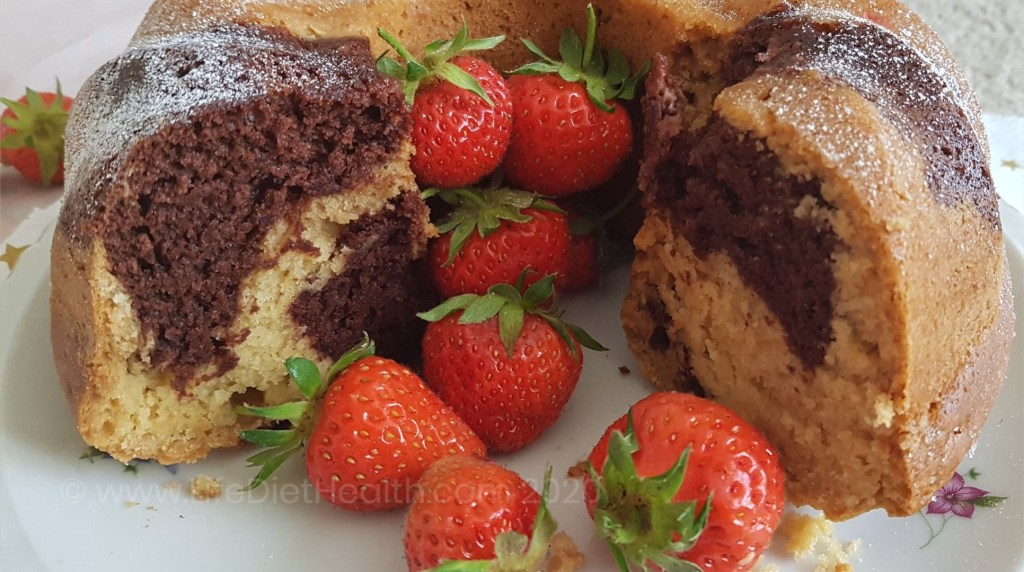 Close up of cut marbled bundt cake with fresh strawberries inside.
