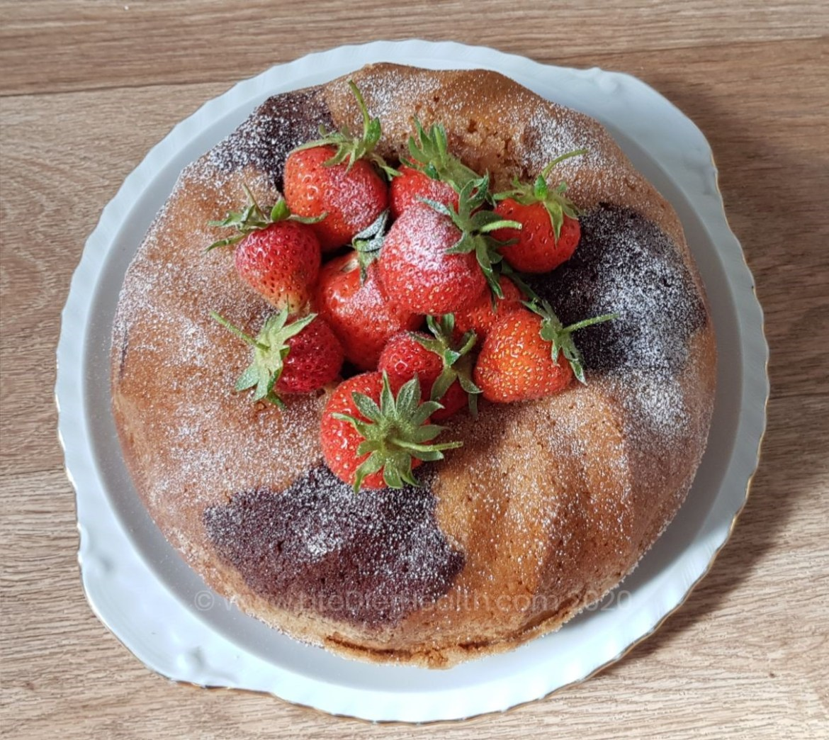 Marble bundt cake on a white and gold rimmed plate, topped with strawberries and dusted with icing sugar