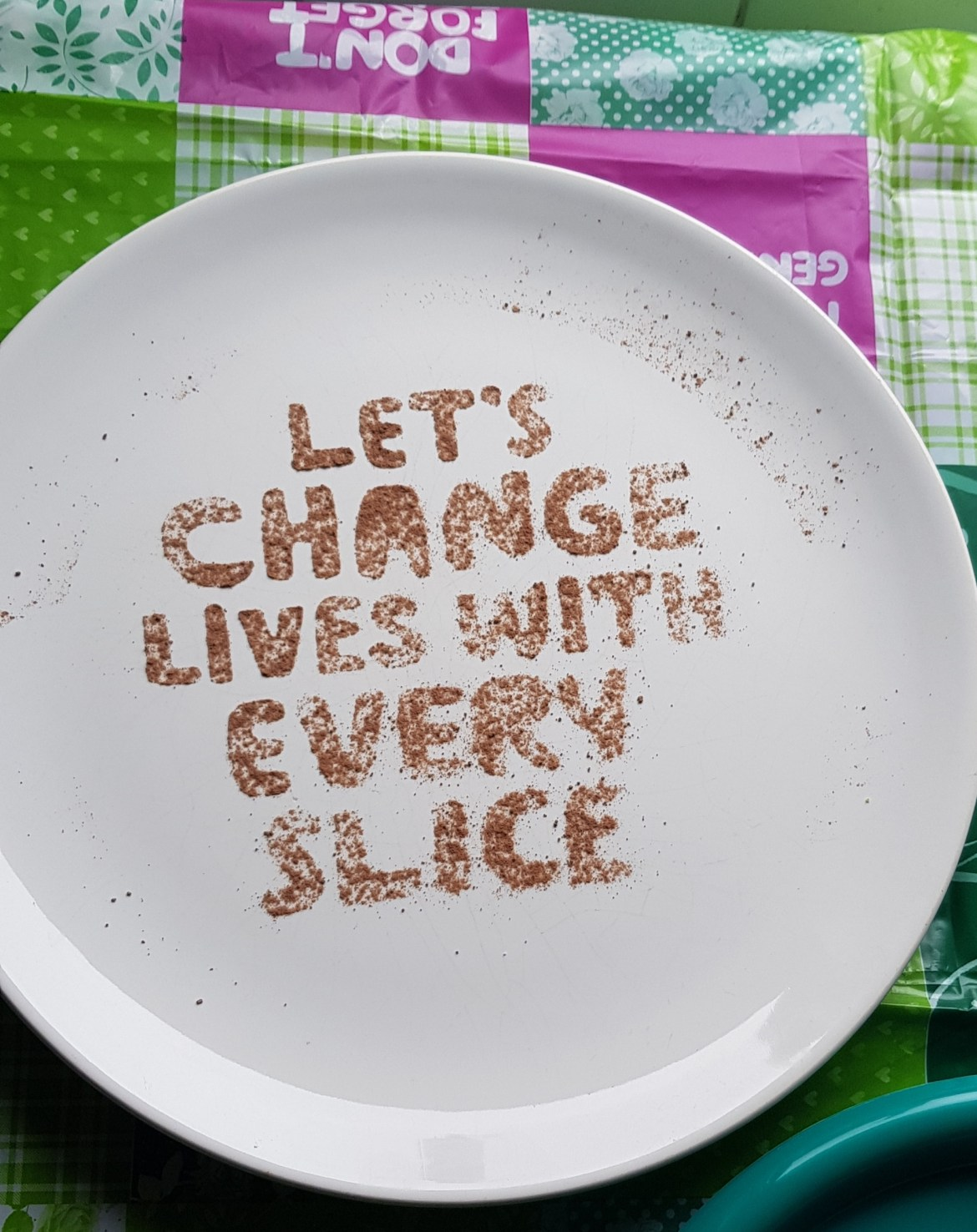 white plate with cocoa dusted words lets change lives with every slice