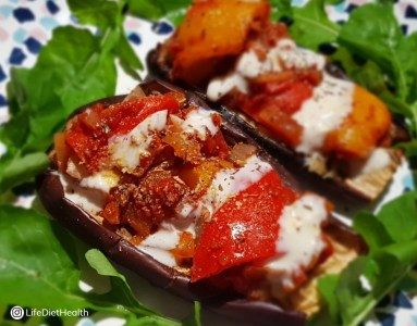 Stuffed aubergines on a bed of rocket with yogurt drizzle