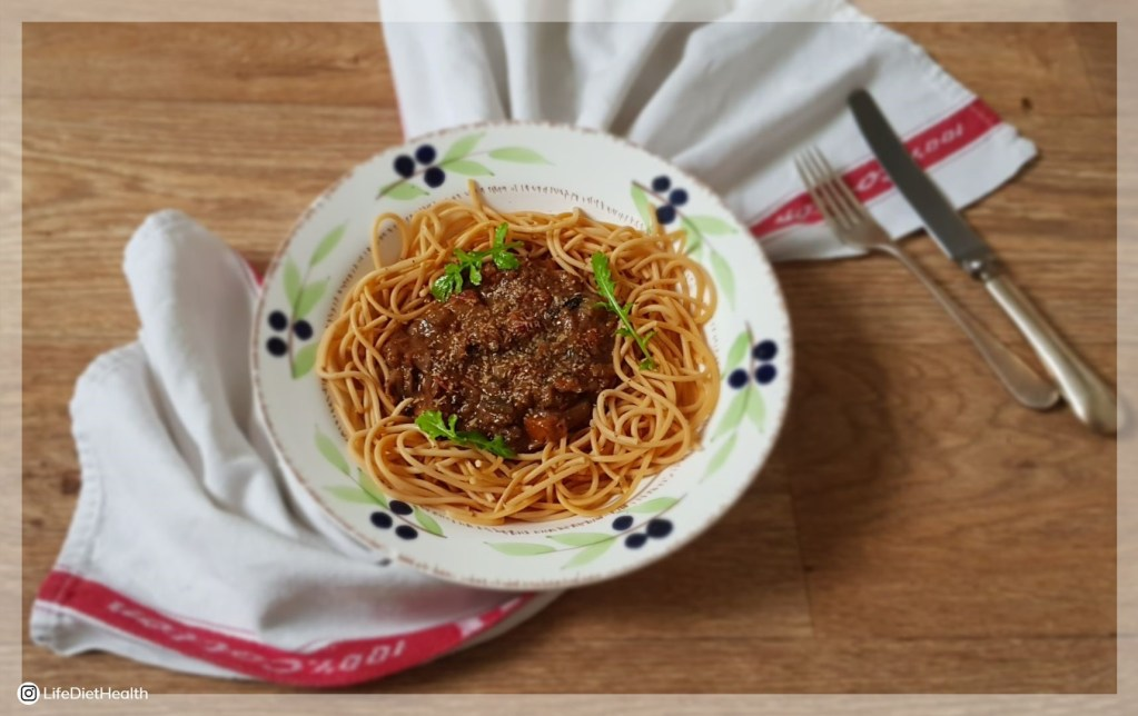 Bowl of spaghetti bolognese on a white tea towel with a knife and fork